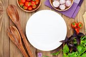 picture of plating  - Fresh farmers tomatoes and basil on wood table with empty plate for copy space - JPG