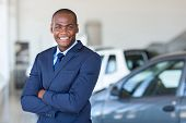 picture of showrooms  - african vehicle dealership principal with arms folded in showroom - JPG