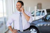 pic of showrooms  - handsome car salesman talking on cell phone in showroom - JPG