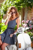 stock photo of scooter  - beautiful italian woman sitting on a italian scooter - JPG
