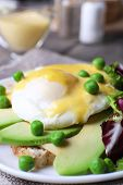 stock photo of benediction  - Toast with egg Benedict and avocado on plate on table close up - JPG