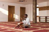 stock photo of muslim man  - Black African Muslim Man Is Reading The Koran - JPG