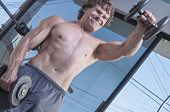 stock photo of dumbbell  - Muscular shirtless Caucasian man with expression of exertion as he raises heavy dumbbell weight while performing front dumbbell raises in gym - JPG