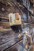 stock photo of hasp  - An old rusty padlock locks a wooden ancient door with rust handle - JPG