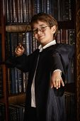 image of magic-wand  - A boy stands with magic wand in the library by the bookshelves with many old books - JPG
