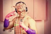 picture of apron  - Funny and handsome muscular man in an apron and headphones singing into a microphone in the pink kitchen - JPG