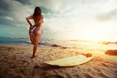image of stretch  - Young lady stretching on the beach before surfing - JPG