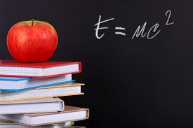 pic of albert einstein  - A pile of coloured books on a desk with a red apple and copy space on a blackboard - JPG