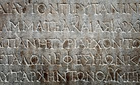picture of chisel  - ancient Greek writing chiseled on brown stone - JPG