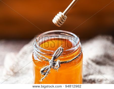 Honey In A Glass Jar With Honey Dipper On Vintage Wooden Background Close Up.