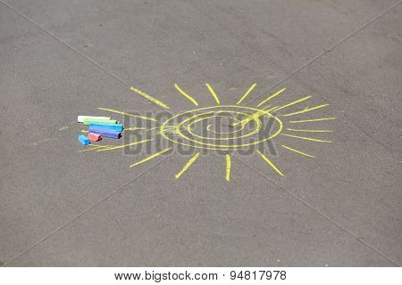 child's drawing of sun and chalks on a street