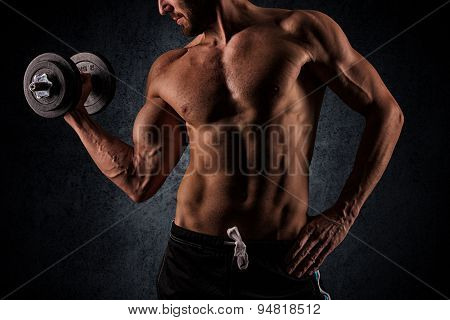 Handsome Muscular Man Working Out With Dumbbells Over Black Background