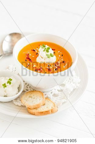 Pumpkin Soup With Cream And Paprika In A White Bowl On A Light Wooden Background