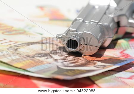 Gun Muzzle On A Pile Of New Israeli Shekels (nis) Banknotes