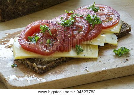 Dark Bread With Cheese And Juicy Tomatoes