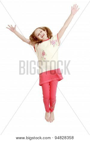 Joyful girl jumping with hands wide apart