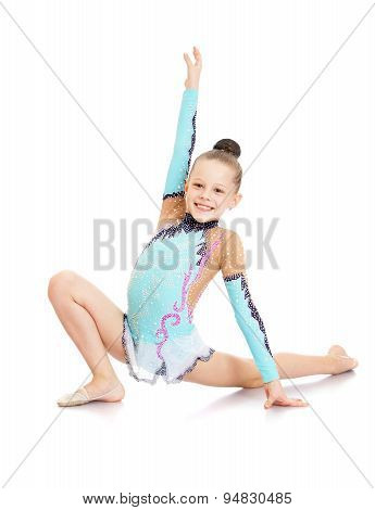 Cheerful girl in a beautiful gymnast sports swimsuit shows exerc