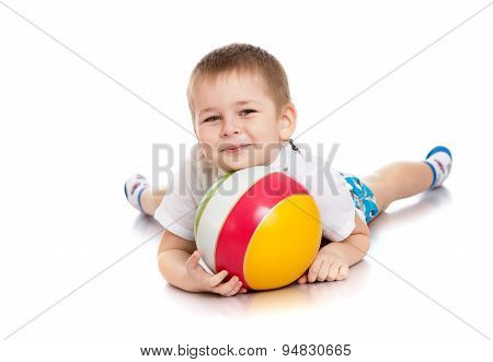 Beautiful little boy lying on the floor hugging striped ball
