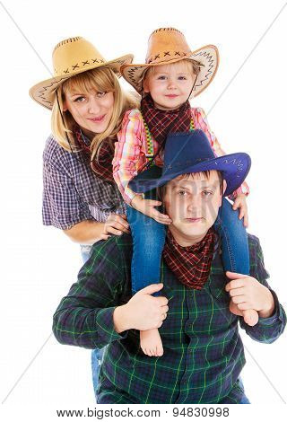 Cheerful young cowboy family in hats, mom dad and little daughte