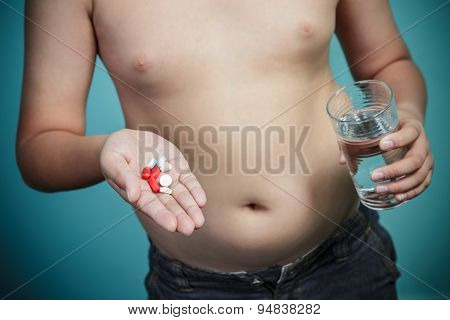 Obese Boy Holding A Lot Of Pills, Healthy And Lose Weight Concept