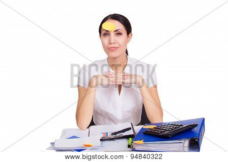 Young business woman sitting in office with clear reminder sticker on her face having an idea. Isola