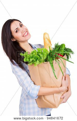Happy young woman holding paper bag with groceries. Smiling girl customer. Consumerism. Isolated