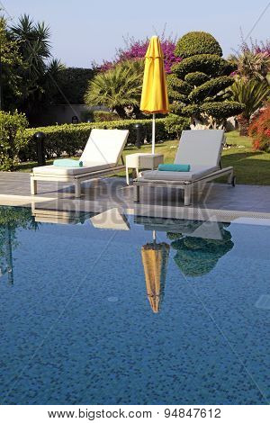 White Outdoor Furniture And Yellow Umbrella Near The Swimming Pool