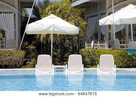 White Sun Beds In The Swimming Pool For Relax On Beautiful Summer Resort