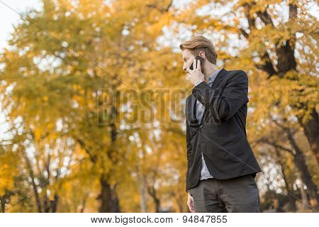 Young Man With Mobile Phone In The Autumn Park