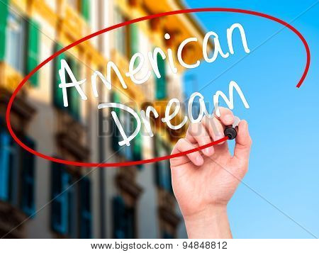 Man Hand writing American Dream with black marker on visual screen.