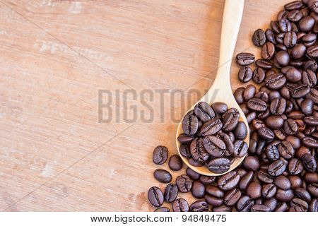 Coffee Beans In Wooden Spoon On Wooden Table Background