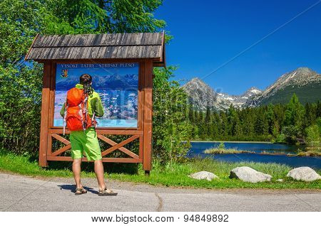Man watching map of mountain trails by lake
