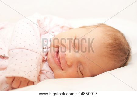 Smiling Newborn Baby Sleeping On White