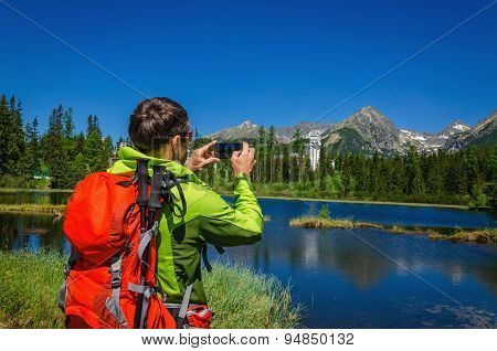 Man takes picture of beautiful mountain lake