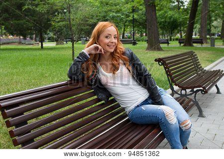 Beautiful Blond Woman Sitting On Bench