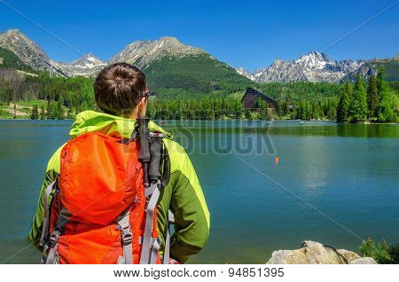Young man admires high mountains and lake Slovakia