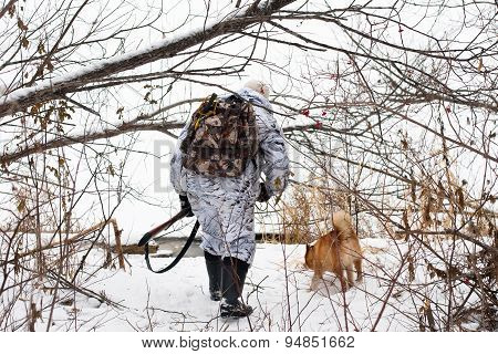 Hunter With Dog Edges One's Way Through The Shrubs