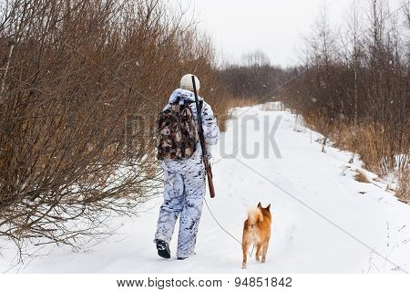 Hunter With His Dog Walking On The Winter Road