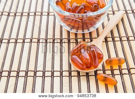 Fish Oil Capsules In Wooden Spoon On Bamboo Mat