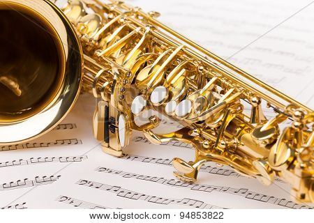 Beautiful golden alto saxophone on musical notes