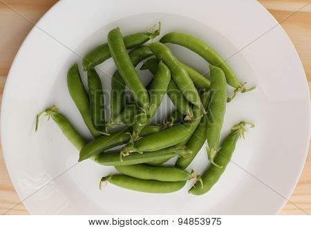 Green Pea Pods In White Plate On Wooden Table