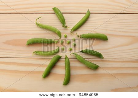 Green Peas  And Pea Pods On Wooden Table