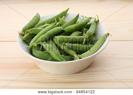 Green  Pea Pods In White Dish  On Wooden Table