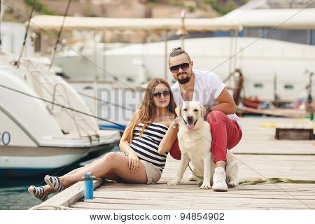 Young couple on a walk in the Harbor with a white Labrador