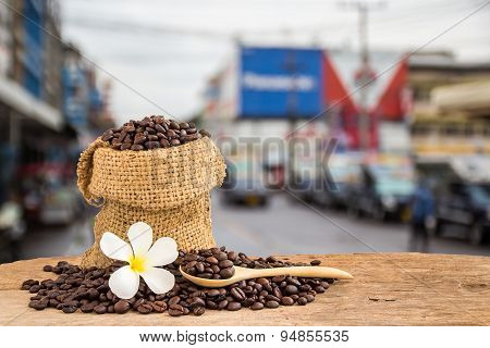 Coffee Beans In Burlap Sack On Wooden Table With Blur Background