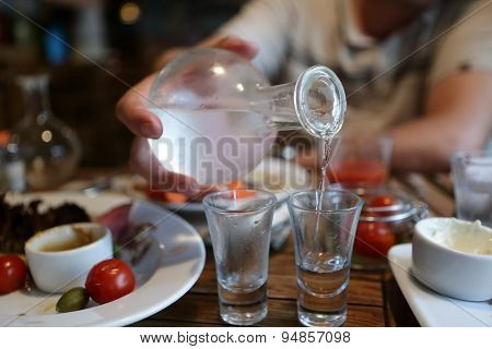 Man Pouring Vodka From The Decanter