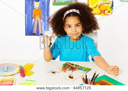 African girl puts puzzle pieces together at  table