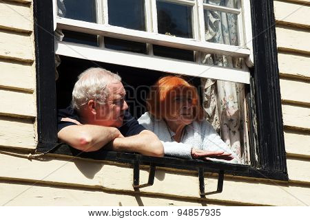 Elderly couple look out from their window