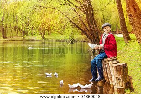 Boy sit near pond playing with white paper boats