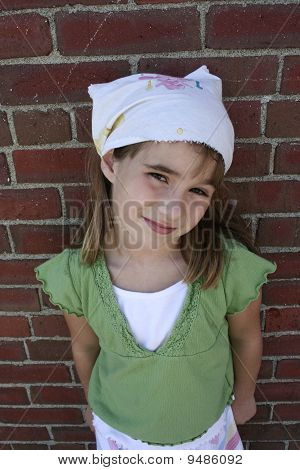 Little girl leaning against brick wall